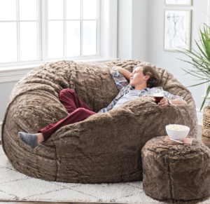 Young man relaxing on LOVESAC furniture with a drink