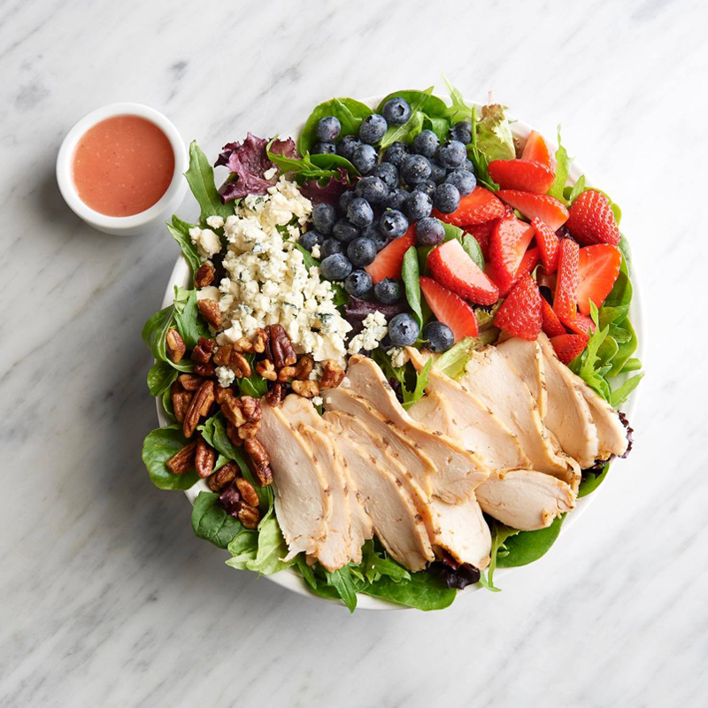 Sliced chicken salad with walnuts, strawberries, blueberries, and feta cheese, all served on lettuce