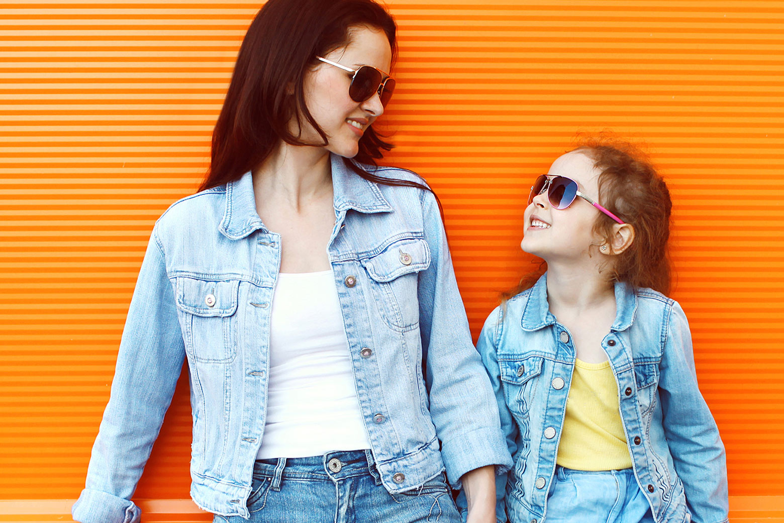 Mom and daughter in denim smiling at each other, against an orange background