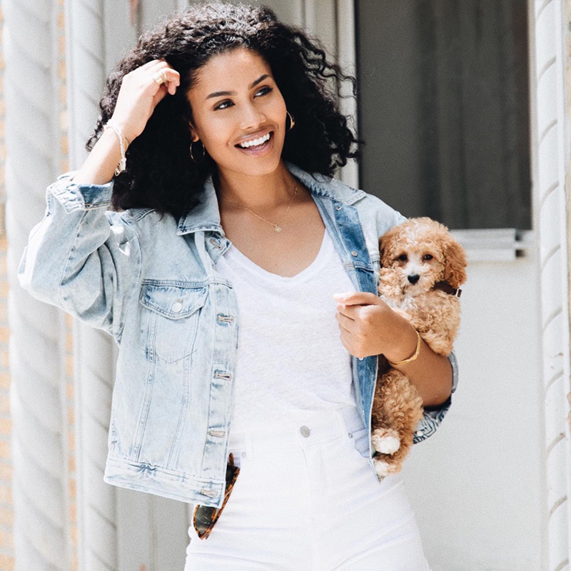 Young woman with black hair, wearing denim jacket and white dress, holding her puppy