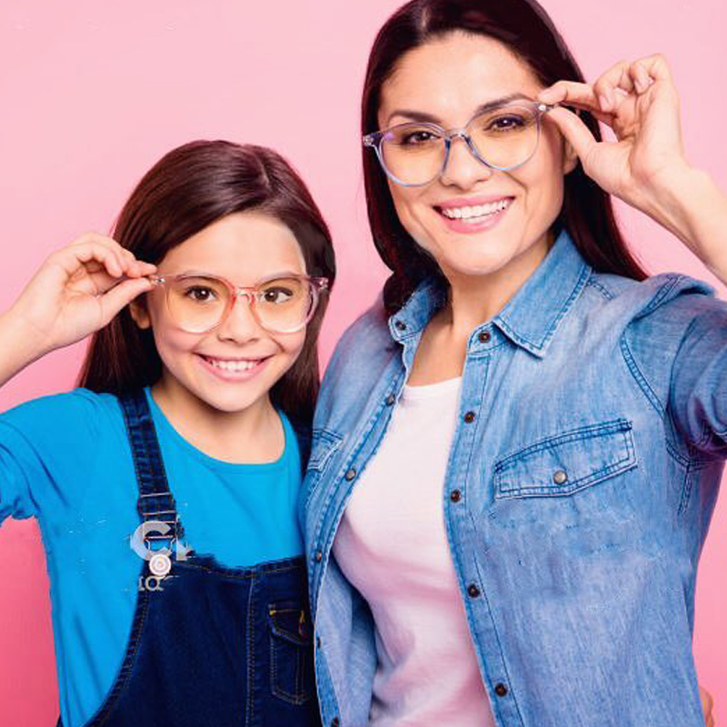 Little girl and her mom smiling, wearing their new glasses