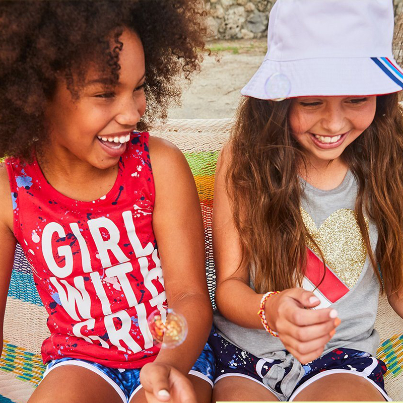 Two young friends laughing together, one wearing shirt that says Girls Have Grit, and the other wearing a shirt with a giant heart