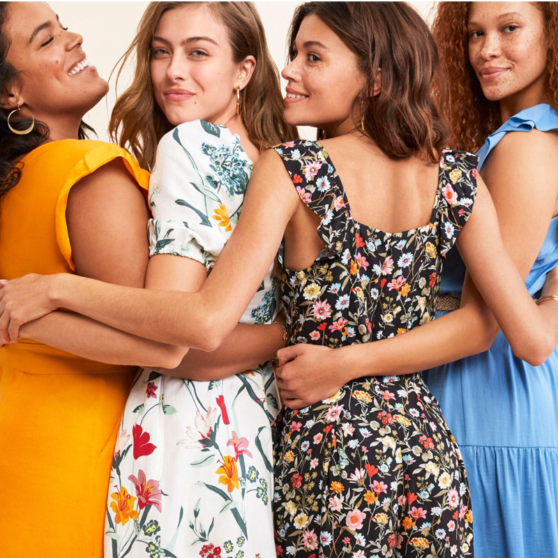 Group of four girlfriends wearing cute dresses in organge, flowered patterns, and sky blue colors