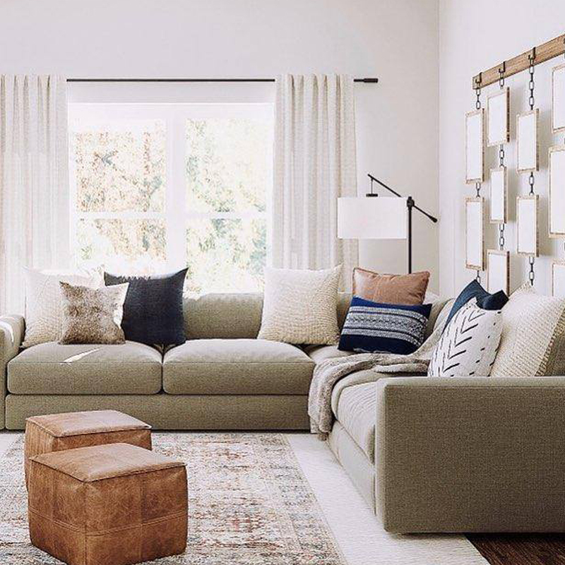 Living room couches with pillows, plus ottomans and art