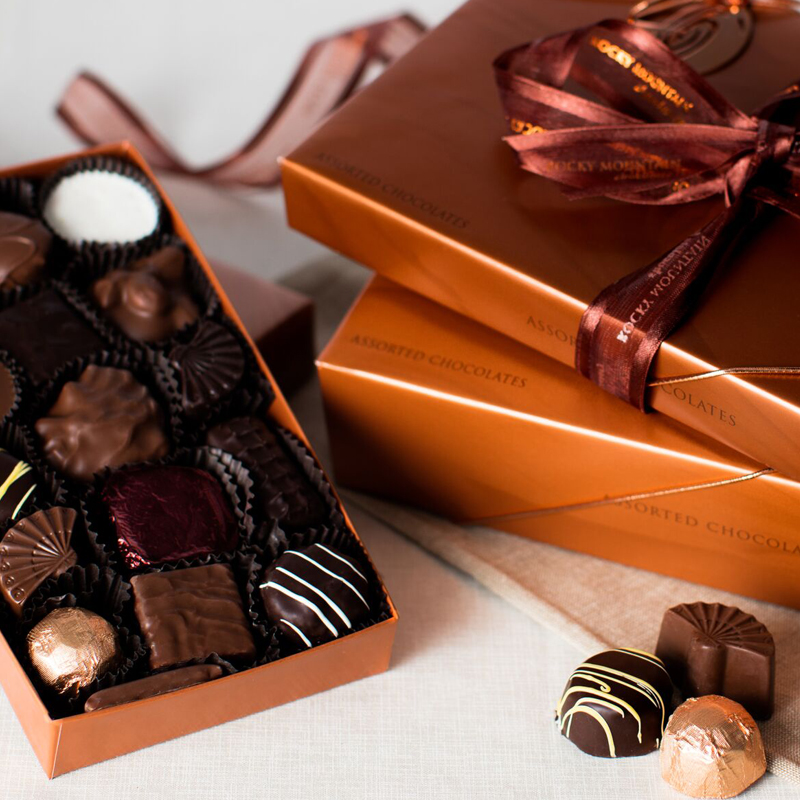 A box of various chocolates with gift wrapped top, plus truffles