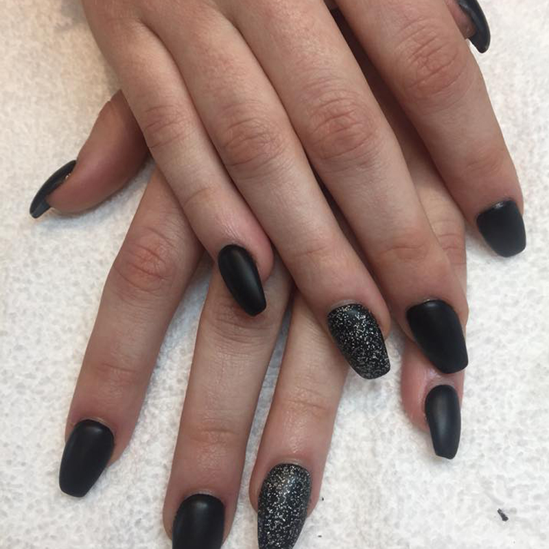 Woman's hands with manicured black nails, one nail on each hand is sparkly