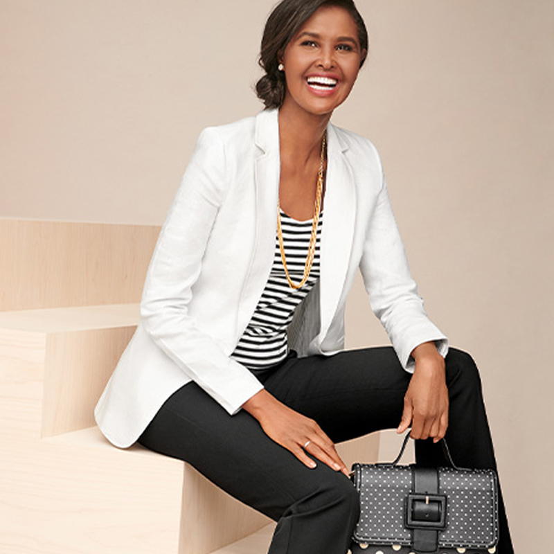 Smiing young black woman wearing a white jacket, black and white striped blouse, and black pants, holding a white and black polkadot handbag