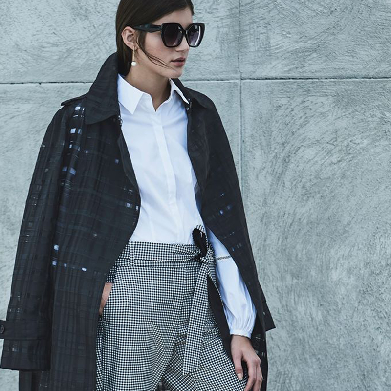 Stylish young brunette woman wearing sunglasses, in a black jacket, white blouse, and gray slacks