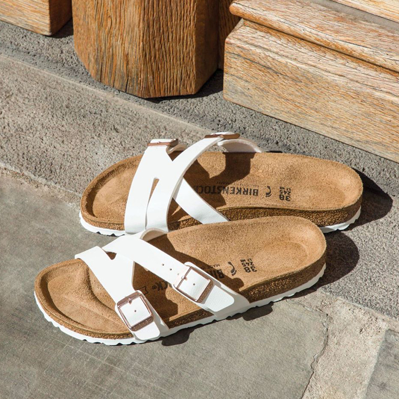 Pair of white sandals with tan soles