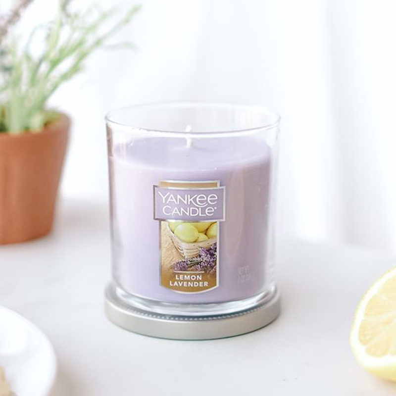 Beautiful lilac candle sitting on counter with plant